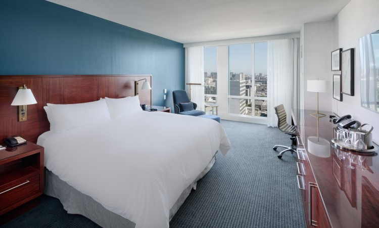 guest room with white linens and floor to ceiling windows with a view of the city