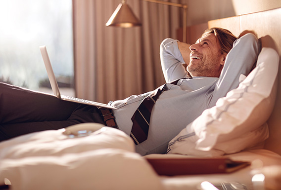 well dressed man laying on top of a guest bed with his laptop smiling