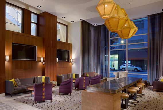 modern lobby area with couch seating, table with stools, and modern design elements