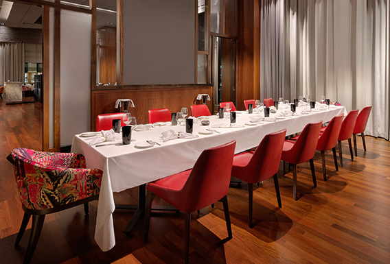 private dining room with one long table surrounded by red chairs