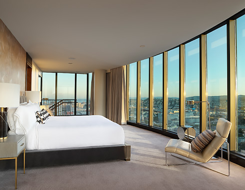 guest room with the bed facing the floor to ceiling windows overlooking the city