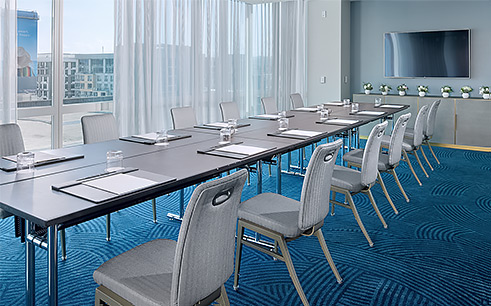 conference room at a hotel with blue carpet, long conference table with chairs, and a tv on the wall