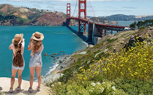 two women wearing hats standing on a rock overlooking the ocean and red golden gate bridge