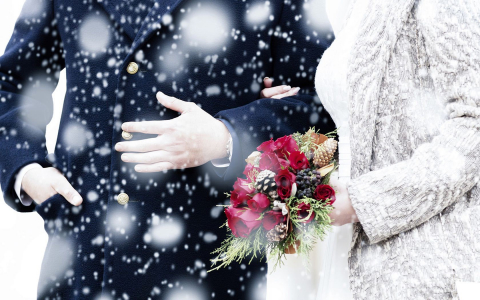 man and woman walking in the snow with a flower bouquet