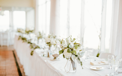 long table with white table clothes and floral place settings