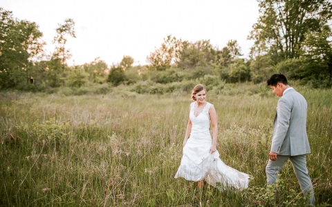bride and groom walking a field