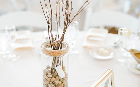 table center piece of vase with pebbles and twigs