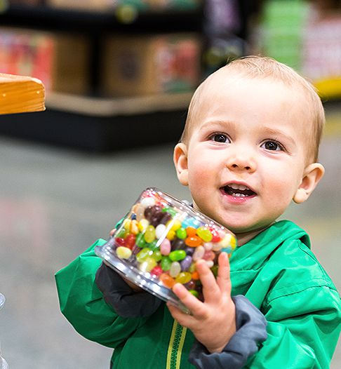 little boy holding a jar of jelly beans