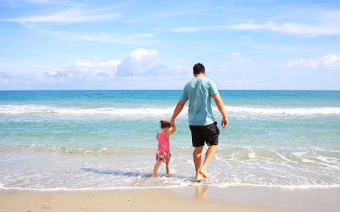 father and daughter walk along the beach