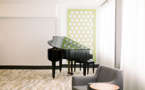 piano in corner of lobby with a chair next to it