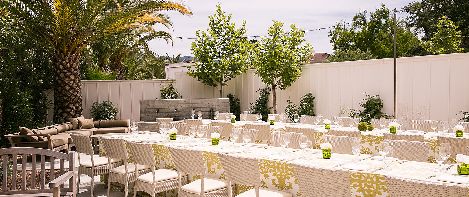 two long wedding tables decorated on an outdoor terrace