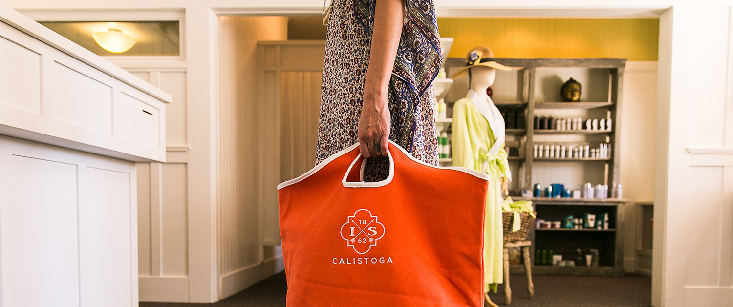 a woman walks in a store holding a red bag with the Indian springs Calistoga logo on it