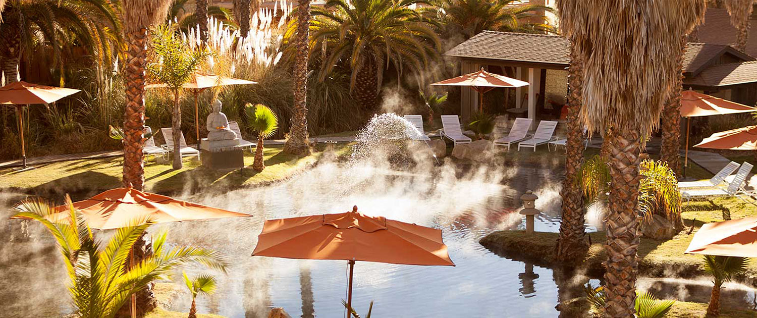 Heated pool with white lounge chairs and orange umbrellas