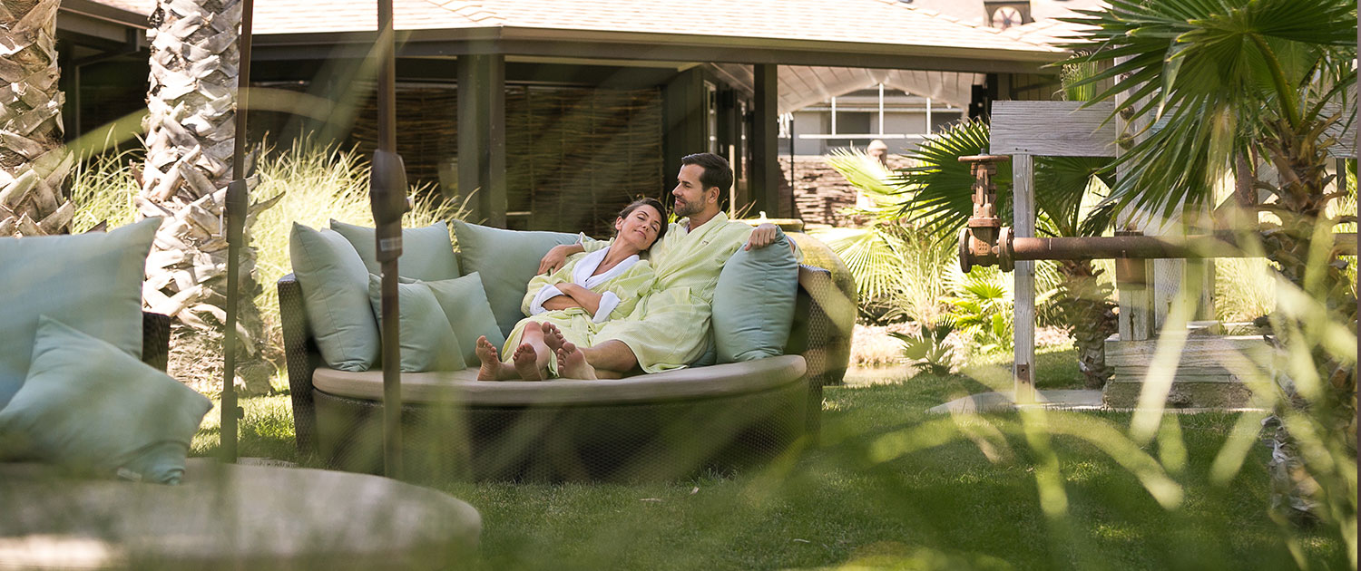 a man and woman sitting on a rounded couch on a grassy patio wearing robes