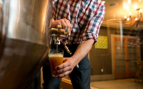 a man pouring draft beer into a glass
