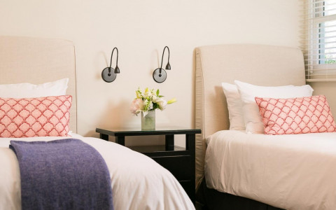 two twin beds with tan headboards, white sheets, and navy and coral accents