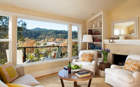 neutral colored living room area with a view of the outdoor balcony from the window