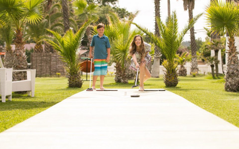 a mom and son playing shuffle board on a grass patio