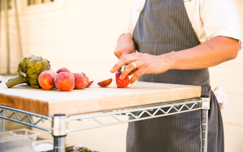 a chef cutting apples on a wood cutting board