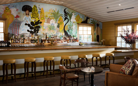 bar area with a colorful wall mural behind the bar and orange backless barstools