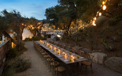 long outdoor dining table lit up with lights at night and string lights hanging from the trees