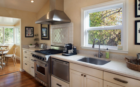 kitchen area with stainless steel appliances and a window over the sink