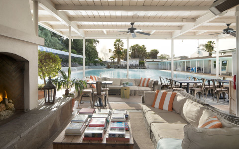 covered outdoor lounging and seating area next to the pool with a fireplace and ceiling fans hanging above