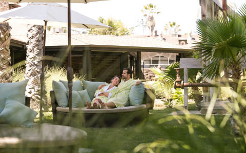 a man and woman sit together in a round lounging couch on a grass patio area