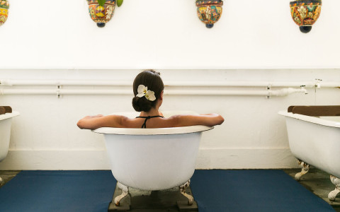 a woman sitting in a stand alone tub facing the wall