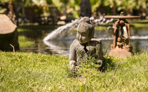 a small buddha statue sitting on grass near a pond