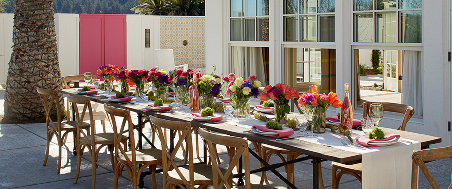 long dining table on an outdoor patio decorated with bright colored flower centerpieces