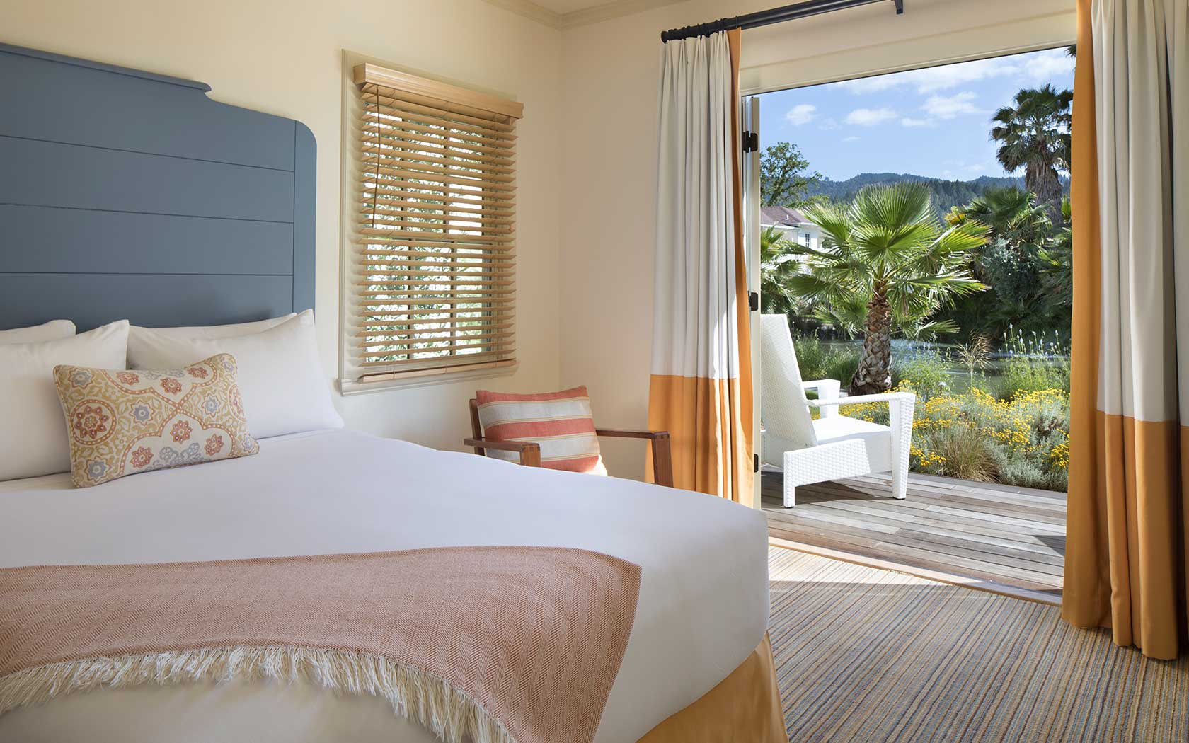 guest room with white sheets, orange accents colors, blue headboard, and a sliding glass door open leading to an walkout outdoor terrace