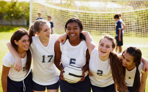 Group of young girls in uniforms holding volleyball