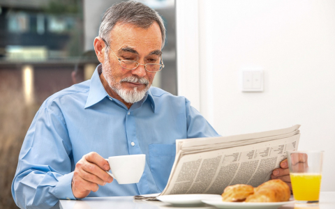 Older man reading newspaper at table with cup of coffee in other hand