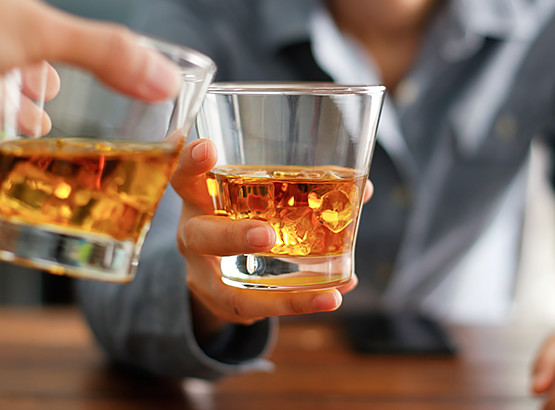 Close up of two people toasting with whiskey
