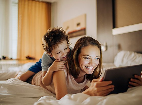 Little boy laying on mother's back as they look at tablet