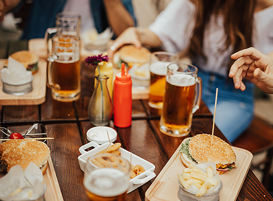 Table with burgers & mugs with beer