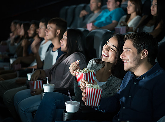 Couple watching movie in theater with popcorn