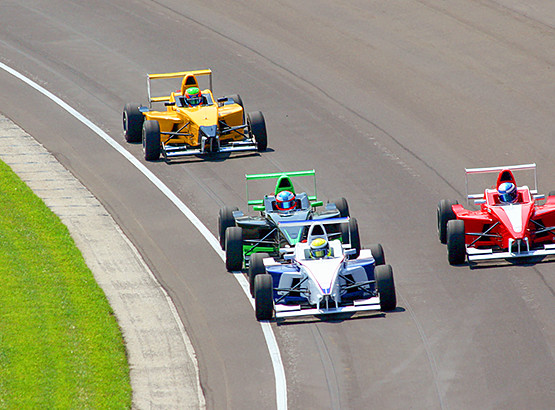 Indy race cars riding along track