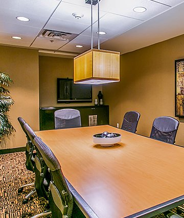 Room with rectangular wooden table & black chairs set for meeting