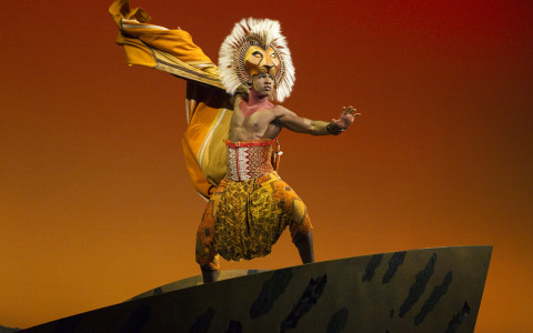 Actor in lion costume performing in The Lion King on Broadway