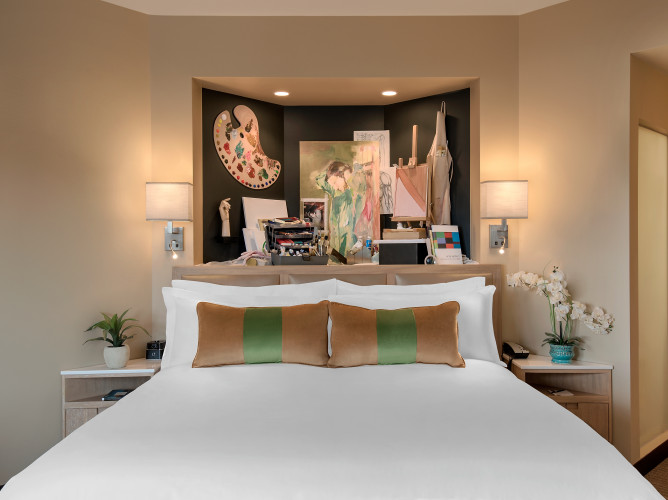 Artistically themed room with a white queen bed