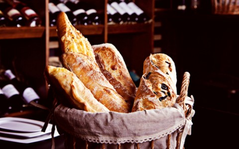 fresh bread in basket with bottles of wine on background