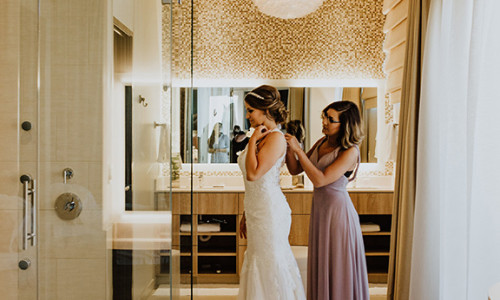 bridesmaid helping bride get dressed