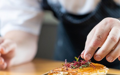 chef plating a fish dish