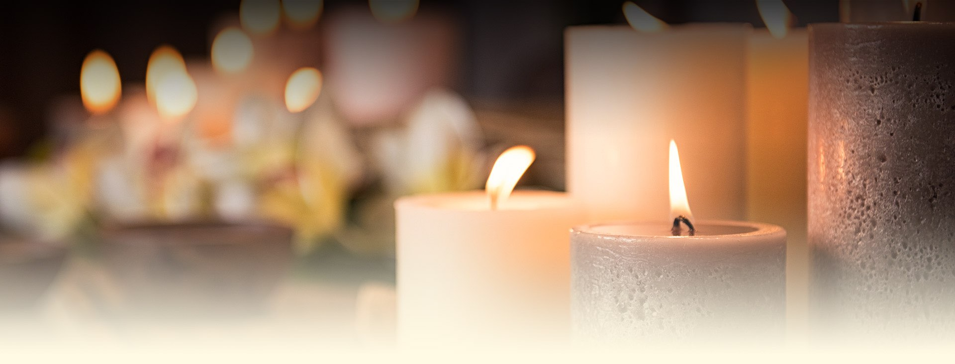 closeup of white and tan lit candles