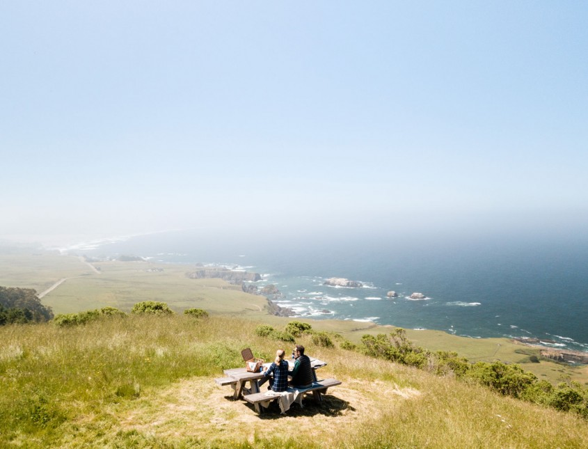 cliff with couple sitting at picnic table