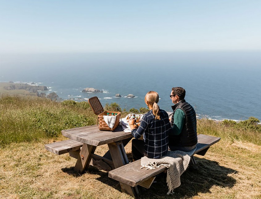 man and woman having a picnic at a picnic table overlooking the ocean cliff