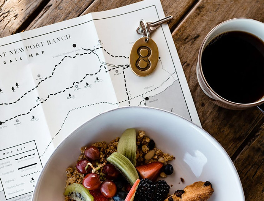 a property map, room key, granola and coffee on a table