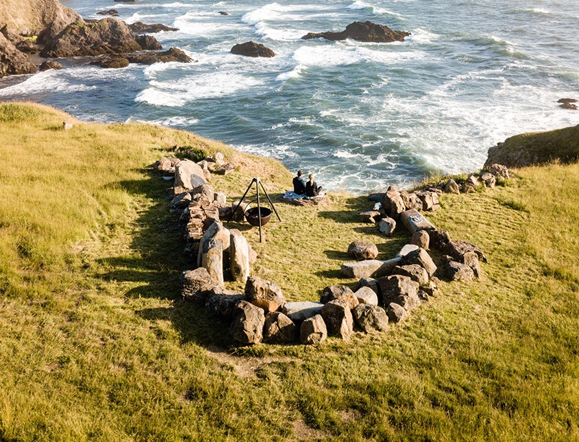 fire pit surrounded by large rocks in a u shape overlooking the ocean